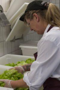 Küchenhilfe Birgit mischt Dressing unter einen Salat. (Foto: Susanne Link)